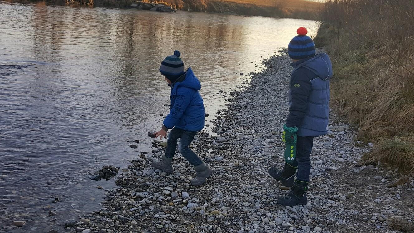 Mit Steinen im Winter am Fluss spielen
